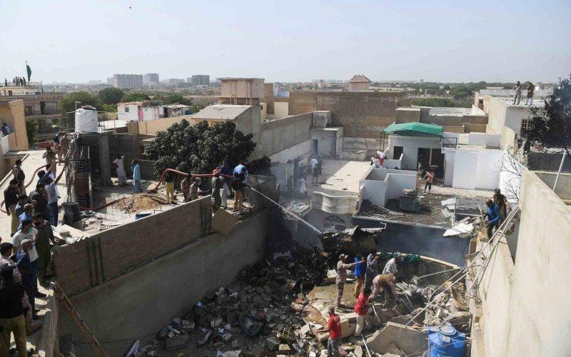 Petugas penyelamat memadamkan puing-puing yang terbakar di lokasi kecelakaan, di Karachi, pada 22 Mei/Bloomberg - AFP vi Getty Images/Asif Hassan