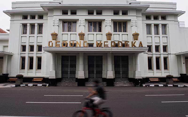 Warga melintas di depan Gedung Merdeka saat Pembatasan Sosial Berskala Besar (PSBB) di Bandung, Jawa Barat, Sabtu (18/4/2020). ANTARA FOTO - M Agung Rajasa