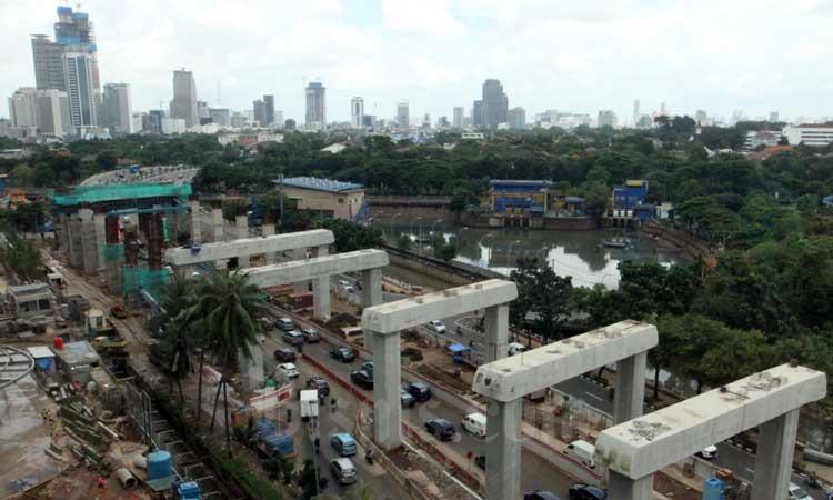 Kendaraan roda empat dan dua melintas di dekat proyek pembangunan  konstruksi Lintas Rel Terpadu (LRT) Jabodetabek di Jakarta, Rabu (26/2/2020). Bisnis - Dedi Gunawan