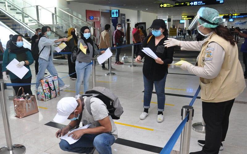 Petugas karantina meminta dokumen kesehatan para pemudik Warga Negara Indonesia (WNI) saat tiba di terminal kedatangan internasional Bandara Kualanamu Kabupaten Deliserdang, Sumatera Utara, Kamis (21/5/2020). Sebanyak 83 WNI dengan visa melancong yang terdampak karantina (lockdown) pandemi Covid-19 di Malaysia itu tiba dan langsung mengikuti prosedur pemeriksaan protokol kesehatan Covid-19 sebelum pulang ke daerah masing-masing. - Antara/Septianda Perdana
