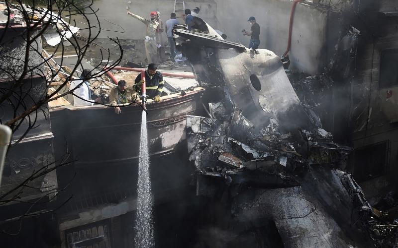 Petugas penyelamat memadamkan puing-puing yang terbakar di lokasi kecelakaan, di Karachi, pada 22 Mei/Bloomberg - AFP vi Getty Images - Asif Hassan