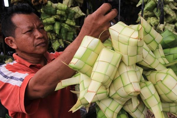 Pedagang menata ketupat yang terbuat dari daun kelapa atau janur di Kota Meulaboh, Aceh Barat, Aceh, Minggu (2/6/2019). - ANTARA / Syifa Yulinnas.