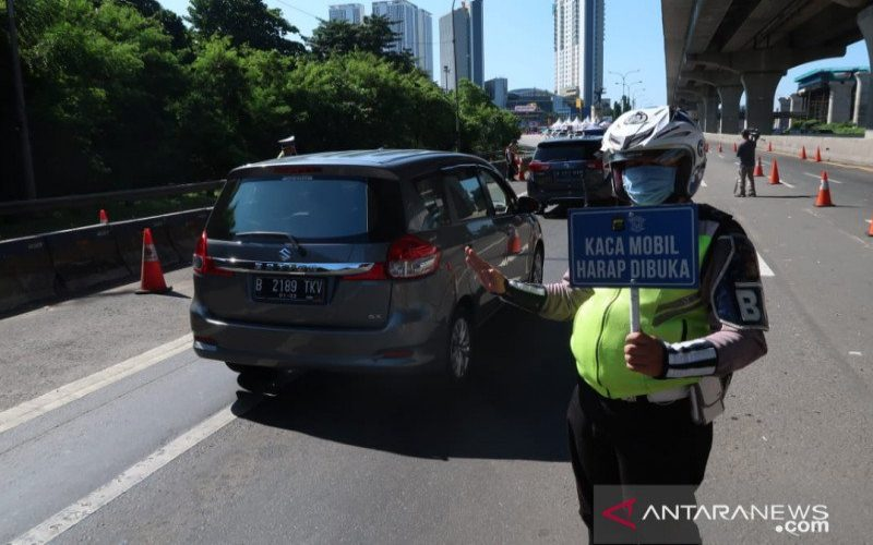 Petugas Kepolisian meminta pengendaraan membuka kaca jendela saat melintasi pos penyekatan arus mudik di jalan tol Jakarta-Cikampek, Bekasi, Jawa Barat, Ahad (24/5/2020).  - ANTARA.