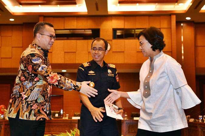 Menteri Keuangan Sri Mulyani (kanan) bersiap menjabat tangan Chairman University Network for Indonesia Export Development (UNIED) Arif Satria (kiri) disaksikan Dirjen Bea Cukai Heru Pambudi (tengah) saat menghadiri peluncuran hasil pengukuran dampak ekonomi fasilitas Kawasan Berikat (KB) dan Kemudahan Impor Tujuan Ekspor (KITE) di Kantor Kemenkeu, Jakarta, Senin (18/2/2019). - ANTARA/Sigid Kurniawan