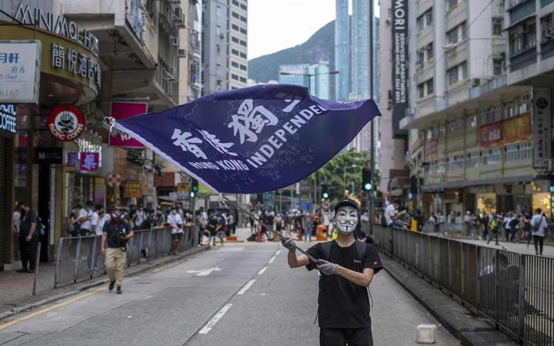 Seorang demonstran yang mengenakan topeng Guy Fawkes mengibarkan bendera