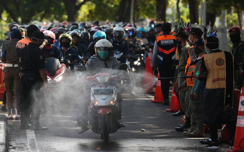 Petugas menyemprotkan larutan disinfektan ke kendaraan bermotor yang memasuki Surabaya di pintu keluar Jembatan Suramadu, Surabaya, Jawa Timur, Senin (20/4/2020). - Antara/Didik Suhartono