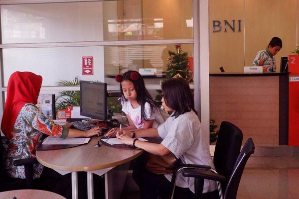 Karyawan melayani nasabah di kantor cabang PT Bank Negara Indonesia Tbk, di Jakarta, Kamis (3/1/2019). - Bisnis/Nurul Hidayat