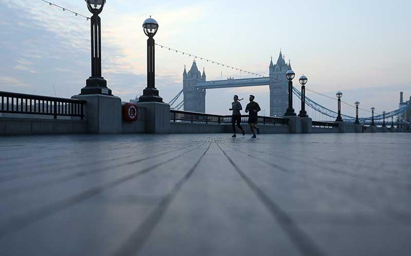 Warga melewati Menara Bridge di tengah lockdown di London, Inggris, Kamis (9/4/2020). - Bloomberg/Simon Dawson