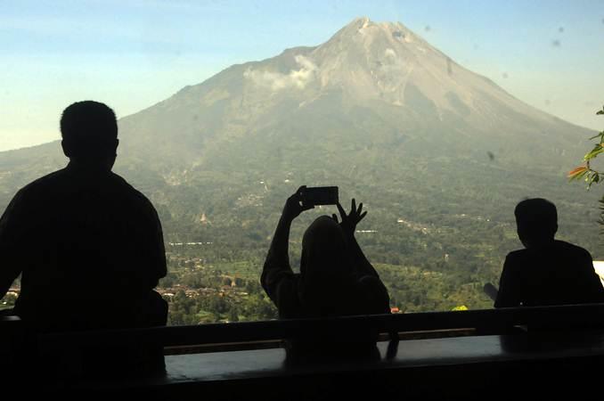 Warga melihat pemandangan Gunung Merapi. - Antara