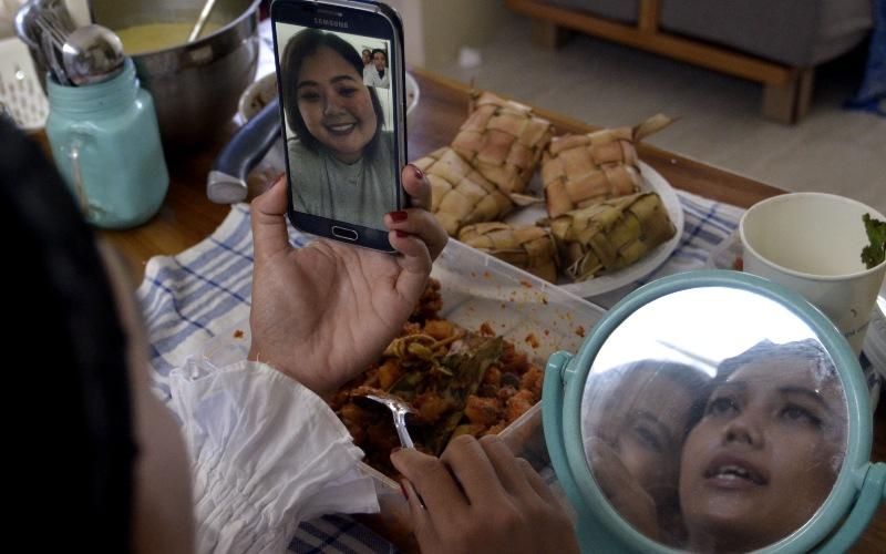 Warga melakukan silaturahmi Idul Fitri 1441 H secara virtual di kawasan Jimbaran, Badung, Bali, Minggu (24/5/2020). Silaturahmi lebaran secara virtual melalui sambungan 'video call' tersebut dilakukan warga sebagai upaya untuk mengantisipasi penyebaran COVID-19. - ANTARA FOTO/Fikri Yusuf