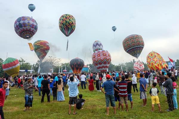 Warga melepaskan balon ke udara saat mengikuti Java Balloon Festival di Pekalongan, Jawa Tengah, Kamis (21/6/2018). - ANTARA/Harviyan Perdana Putra