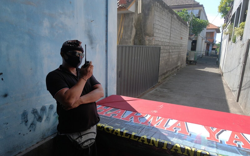 Pecalang atau petugas keamanan adat Bali berkoordinasi menggunakan radio komunikasi saat menjaga kawasan yang diisolasi di Desa Padangsambian Klod, Denpasar, Bali, Selasa (26/5/2020). Sebanyak 75 warga di kawasan tersebut tidak diizinkan keluar wilayahnya hingga 8 Juni 2020 menyusul adanya seorang warga positif terjangkit COVID-19 sehingga upaya itu ditargetkan bisa menghentikan penularan virus melalui transmisi lokal. - Antara/Nyoman Hendra Wibowo