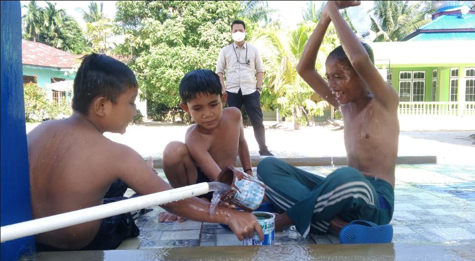 Anak/anak yang sedang menggunakan fasilitas air bersih.