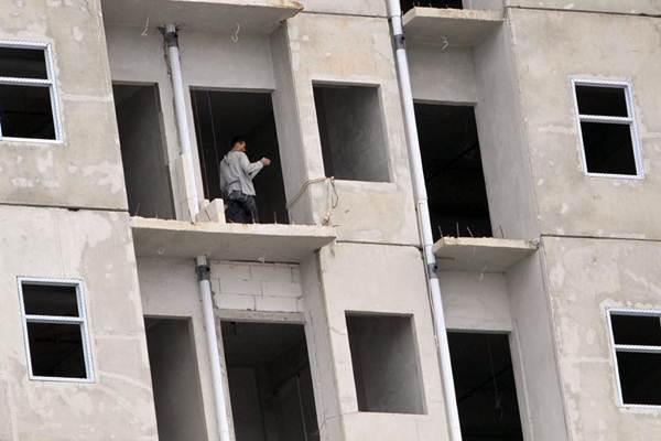 Pekerja beraktivitas di proyek pembangunan gedung bertingkat, di Makassar, Selasa (5/12). - JIBI/Paulus Tandi Bone