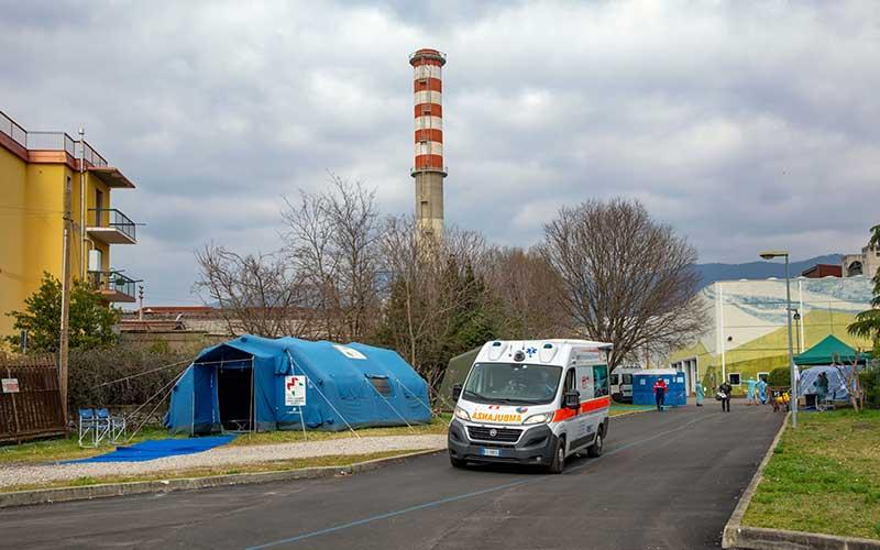 Ambulan melewati tenda dan bangunan darurat yang dibuat untuk membantu sistem perawatan kesehatan di kawasan rumah sakit di Brescia, wilayah Lombardy, Italia, Jumat (13/3/2020)./Bloomberg - Francesca Volpi