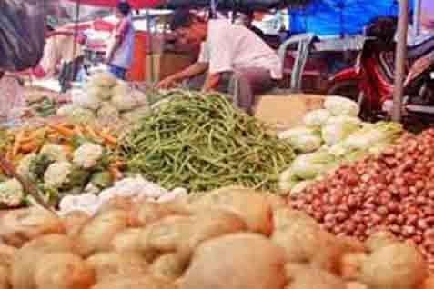 Pedagang menggelar sayuran di pasar