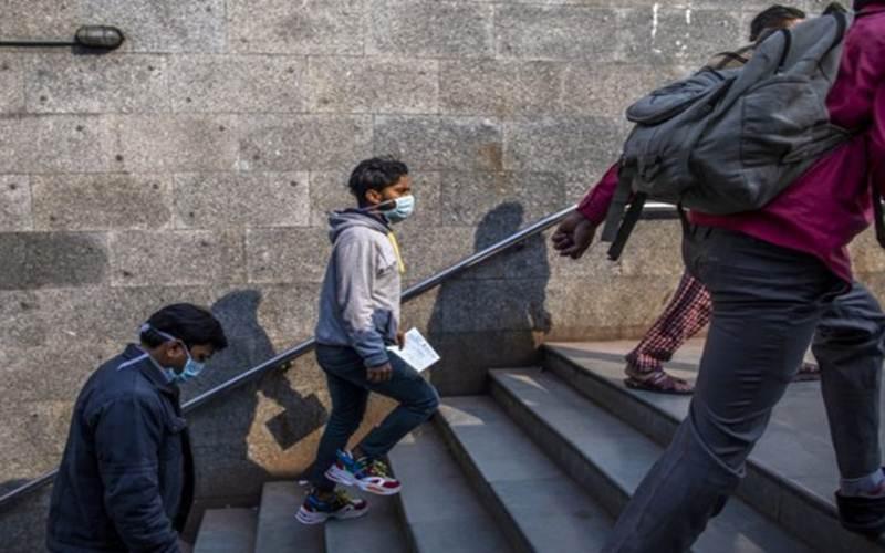 Ilustrasi - Warga di India berjalan sambil menggunakan masker pelindung - Bloomberg/Prashanth Vishwanathan