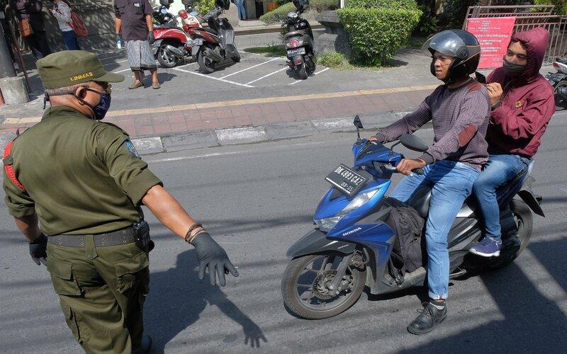 Petugas menghentikan pengendara sepeda motor yang tidak menggunakan masker saat penerapan Pembatasan Kegiatan Masyarakat (PKM) di wilayah Desa Adat Panjer, Denpasar, Bali, Kamis (28/5/2020). Sebanyak lima kelurahan/desa adat di Denpasar mulai menerapkan PKM di wilayahnya masing-masing pada 28 Mei hingga 28 Juni 2020 untuk memutus rantai penyebaran Covid-19. - Antara/Nyoman Hendra Wibowo