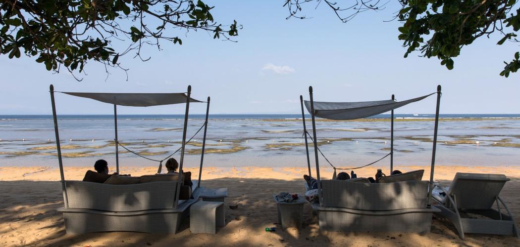 Wisatawan mancanegara bersantai di salah satu pantai di kawasan Nusa Dua, Bali, Indonesia, Rabu (10/10/2018). - Bloomberg/SeongJoon Cho