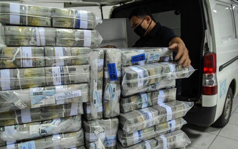 Petugas memasukan uang pecahan rupiah ke dalam mobil untuk didistribusikan dari Cash Center Mandiri, Jakarta, Senin (11/5/2020). - Antara Foto/Muhammad Adimaja