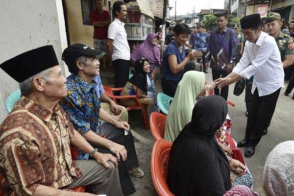 Presiden Joko Widodo (kanan) menyapa lansia disela-sela menyaksikan pembagian paket sembako kepada warga di kawasan Tebet Barat, Jakarta, Kamis (22/6). - Antara/Puspa Perwitasari