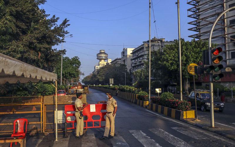 Dua petugas polisi berjaga-jaga di Kota Mumbai, India, seiring dengan pemberlakuan lockdown untuk mencegah penyevaran virus corona Covid-19. - Bloomberg