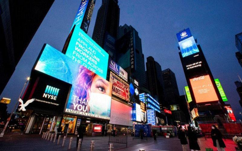 Warga berjalan di sekitar Times Square saat beberapa layar bercahaya biru sebagai bagian dari inisiatif