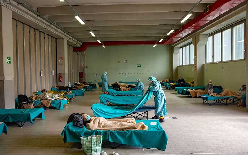 Tenaga medis merawat pasien Covid-19 di tenda dan bangunan darurat yang dibuat untuk membantu sistem perawatan kesehatan di kawasan rumah sakit di Brescia, Lombardy, Italia./Bloomberg - Francesca Volpi