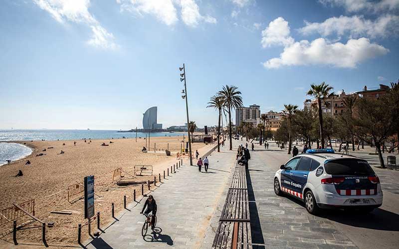 Polisi berpatroli di tepi pantai saat otoritas memberlakukan lockdown di kawasan pantai Barceloneta di Barcelona, Spanyol, Minggu (15/3/2020). - Bloomberg/Angel Garcia