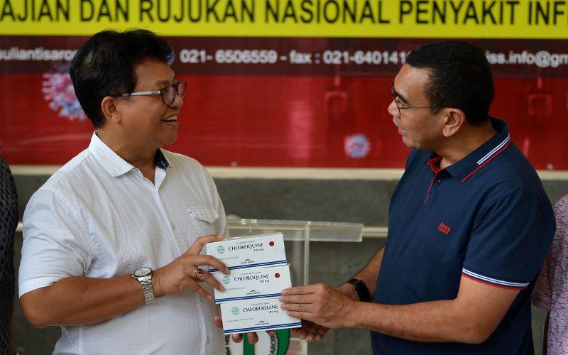 Staf Khusus Kementerian BUMN Arya Sinulingga (kanan) menyerahkan kotak berisi obat Chloroquine kepada Dirut RSPI Sulianti Saroso dr. Moh. Syahril di Jakarta, Sabtu (21/3/2020). - Antara / Aditya Pradana Putra