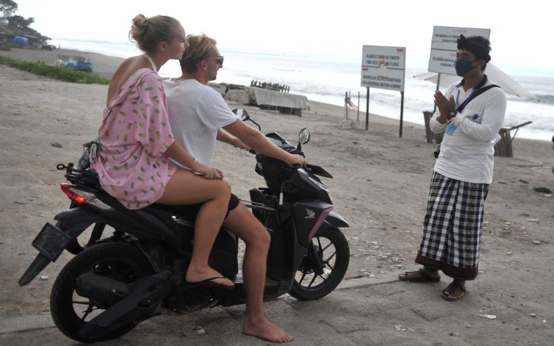 Pecalang atau petugas pengamanan adat Bali memberikan penjelasan kepada wisatawan mancanegara terkait penutupan sementara objek wisata Pantai Batu Belig di Badung, Bali, Rabu (1/4/2020) - Antara/Fikri Yusuf