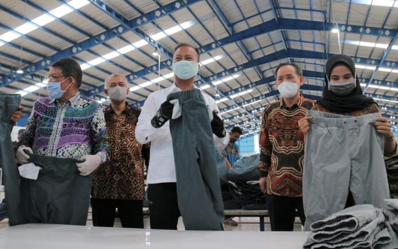 Menteri Perindustrian Agus Gumiwang Kartasasmita (tengah) didampingi Direktur Jenderal Industri Kimia, Farmasi dan Tekstil (IKFT) Muhammad Khayam (kiri) serta Direktur Jenderal Ketahanan, Perwilayahan dan Akses Industri Internasional (KPAII) Dody Widodo (keuda kiri) memperhatikan pakaian produksi PT. Daehan Global di Brebes (29/5/2020). Istimewa - Kemenperin