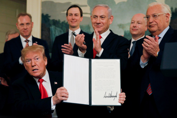 Perdana Menteri (PM) Israel Benjamin Netanyahu (ketiga kanan) bertepuk tangan di belakang Presiden AS Donald Trump (bawah kiri) yang menunjukkan dokumen pengakuan AS atas kedaulatan Israel di Dataran Tinggi Golan dalam sebuah pertemuan di Gedung Putih, Washington, AS, Senin (25/3/2019). - Reuters/Carlos Barria