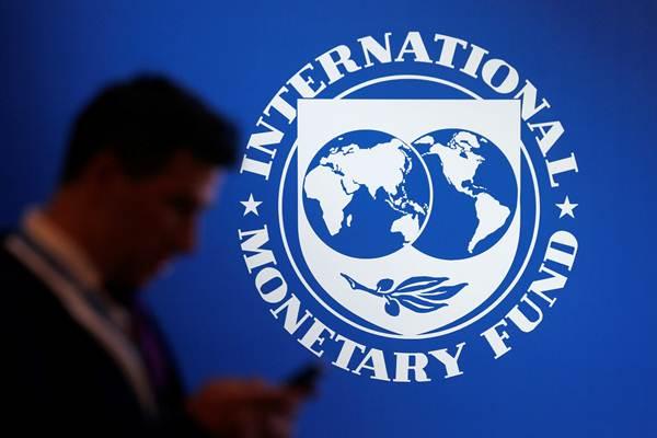 Peserta berdiri di dekat logo Dana Moneter Internasional (IMF) dalam rangkaian Pertemuan IMF - World Bank Group 2018, di Nusa Dua, Bali, Jumat (12/10/2018). - Reuters/Johannes P. Christo