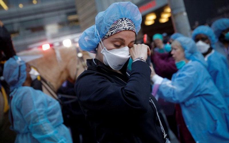Seorang perawat menghapus air matanya saat ia berdiri di luar NYU Langone Medical Center di 1st Avenue di Manhattan saat Polisi New York (NYPD) dan unit lainnya datang untuk menyemangati dan berterima kasih kepada tenaga kesehatan saat penyebaran Covid-19) mengganas di New York, AS, Kamis (16/4/2020)./Antara - Reuters