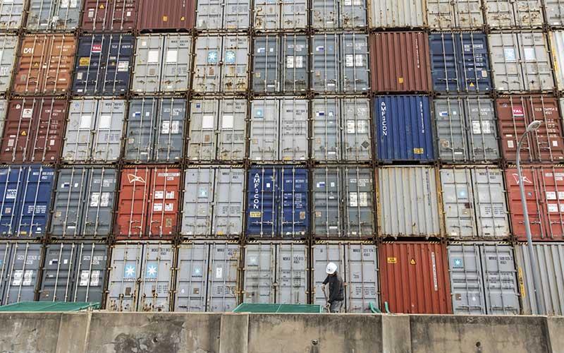 Pekerja berada di depan peti kemas yang ditumpuk di Pelabuhan Yangshan Deepwater, Shanghai, China, Senin (23/3/2020). Bloomberg - Qilai Shen\n