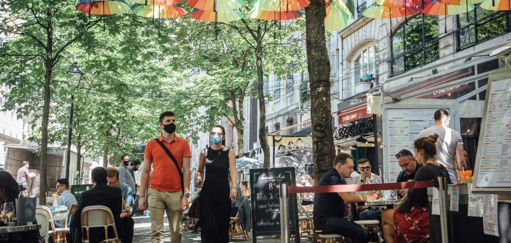 Pejalan kaki mengenakan masker berjalan melewati kafe-kafe yang sudah buka seiring dengan relaksasi lockdown di Paris, Prancis, Selasa (2/6/2020). - Bloomberg/Cyril Marcilhacy
