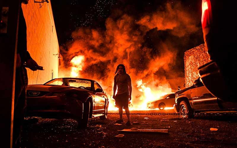 Seorang pria berada di dekat mobil yang terbakar di sebuah garasi parkir saat aksi protes atas kematian George Floyd di Minneapolis, Amerika Serikat, Jumat (29/5/2020). Bloomberg/AFP via Getty Images - Chandan Khanna.