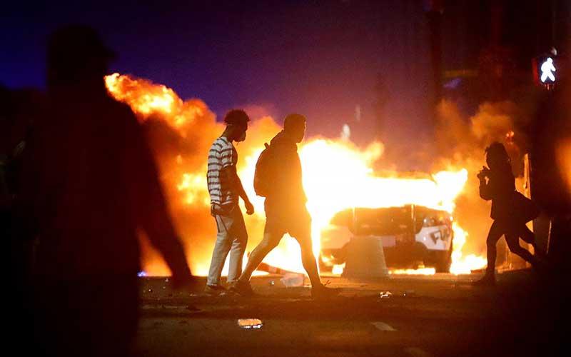 Demonstran berjalan di depan sebuah mobil polisi yang telah terbakar saat protes  atas kematian George Floyd di Boston, Amerika Serikat, Minggu (31/5/2020). Bloomberg/Getty Images - Maddie Meyer