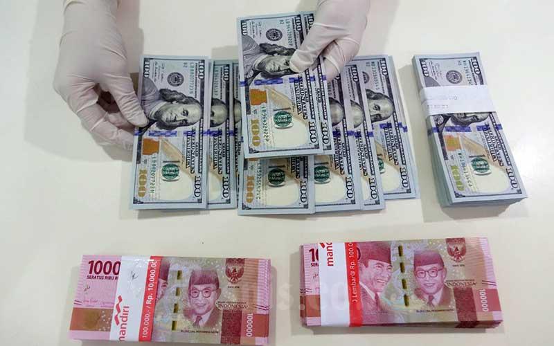 Karyawan menunjukan uang dolar Amerika Serikat (AS) di Jakarta, Rabu (27/5/2020). Bisnis - Eusebio Chrysnamurti