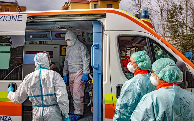 Tenaga medis bersiap mengevakuasi pasien Covid-19 yang tiba dengan ambulans di rumah sakit di Brescia, Lombardy, Italia./Bloomberg - Francesca Volpi