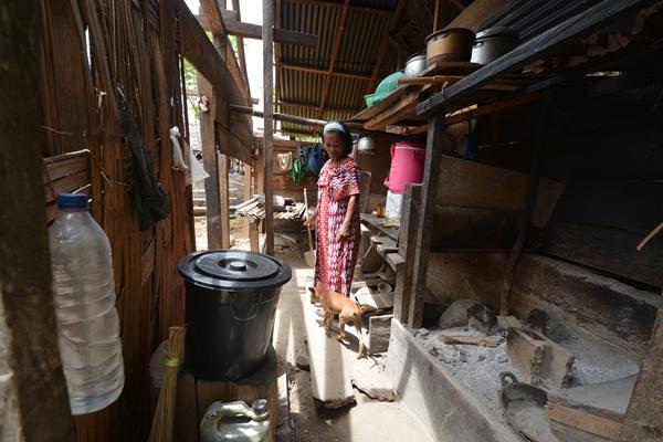 Seorang ibu beraktivitas di rumahnya yang akan menjalani program bedah rumah di Desa Lempelero, Kecamatan Kulawi Selatan, Kabupaten Sigi, Sulawesi Tengah, Rabu (5/4). - Antara