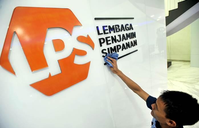 Karyawan membersihkan logo baru Lembaga Penjamin Simpanan (LPS) di Jakarta, Selasa (23/4/2019). - ANTARA/Audy Alwi