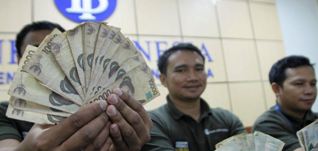 Pegawai Bank Indonesia (BI) Kendari menunjukan uang kertas  Tahun Emisi (TE) 1998. - Antara / Jojon.