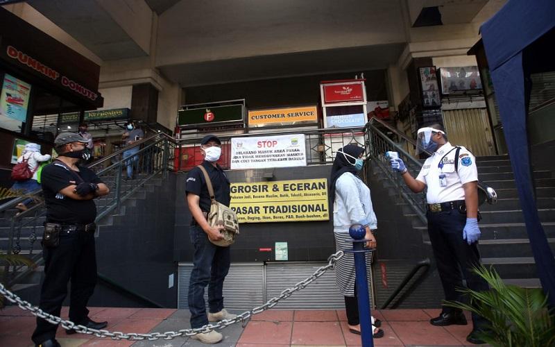 Petugas melakukan thermal scanner kepada para pelayan toko saat akan digelar simulasi standar protokol kesehatan di Pasar Baru Trade Center, Bandung, Jawa Barat, Kamis (4/6). - Bisnis/Rachman