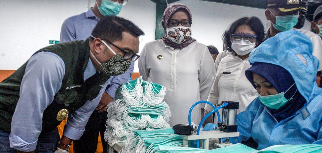 Gubernur Jawa Barat Ridwan Kamil (kiri) didampingi Bupati Bogor Ade Yasin (tengah) melihat produksi pembuatan masker medis di PT Multi One Plus, Gunung Putri, Kabupaten Bogor, Jawa Barat. - Antara / Yulius Satria Wijaya.