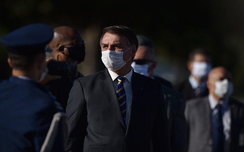 Presiden Brazil Jair Bolsonaro mengunakan masker saat Upacara Bendera di Istana Alvorada di Brasilia  -  Bloomberg / Andre Borges