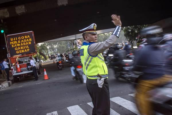 Polisi mengatur arus lalu lintas pada hari pertama uji coba perluasan kawasan ganjil genap di persimpangan Pancoran, Jakarta, Senin (2/7/2018). - ANTARA FOTO/Aprillio Akbar