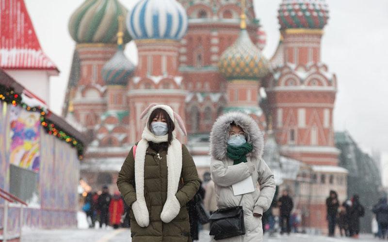 Para pejalan kaki menggunakan masker untuk mencegah penularan virus corona Covid-19 melintas di Lapangan Merah di dekat Istana Kremlin di Moskow, Rusia. - Bloomberg/Andrey Rudakov