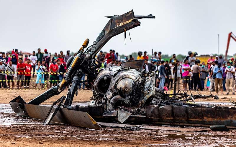 Sejumlah warga menyaksikan bangkai helikopter yang jatuh di Kawasan Industri Kendal (KIK), Kabupaten Kendal, Jawa Tengah, Sabtu (6/6/2020). Belum diketahui penyebab jatuhnya helikopter jenis MI-17 bernomor registrasi HA 5141 milik TNI-AD yang mengakibatkan empat awak tewas dan lima awak lainnya dilarikan ke rumah sakit. ANTARA FOTO/Aji Styawan - WSJ.